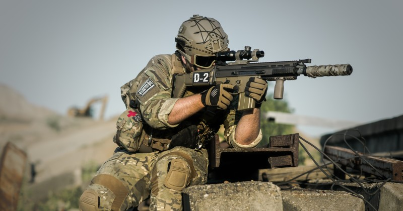A soldier sits on concrete rubble with a semi-automatic rifle